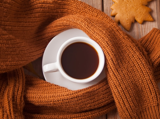 Cup of coffee with cookie and brown sweater on the wooden table Premium Photo