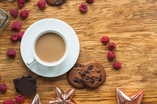 Cup of coffee with cookies; raspberries and chocolate bar pieces on wooden table Free Photo