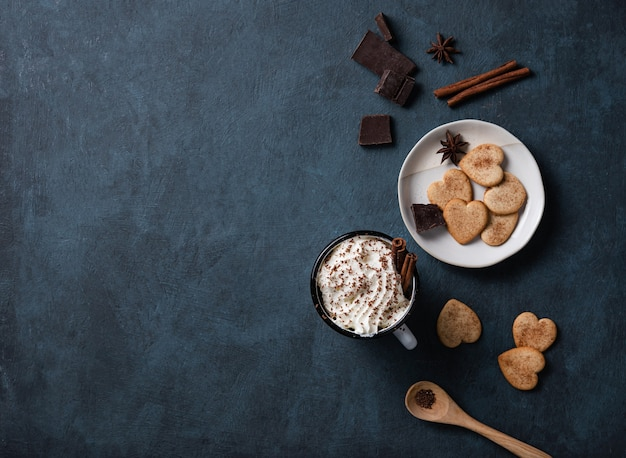A cup of coffee with cream and chocolate chips  on a dark  table with homemade cookies, chocolate and cinnamon. top view, copy space and flat lay Premium Photo