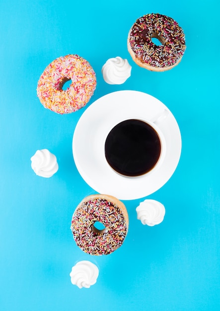 Cup of coffee with donuts and meringues in motion Premium Photo