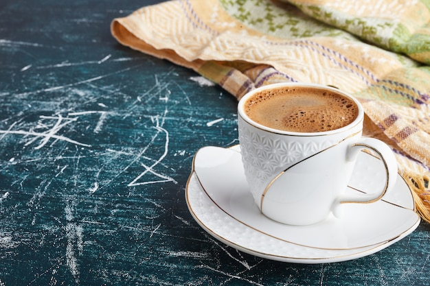 A cup of coffee with foam in a white saucer. Free Photo
