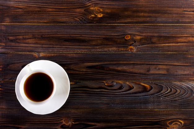 Cup of coffee with foam on wooden table, top view Photo