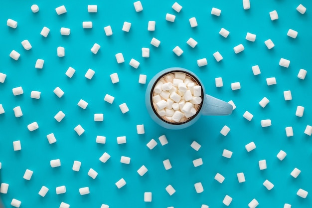 Cup of coffee with marshmallow on blue. Premium Photo