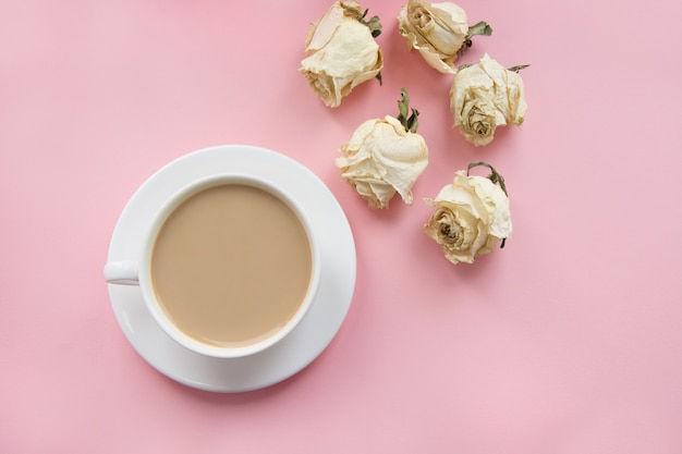 Cup of coffee with milk on pink and dry roses. Premium Photo