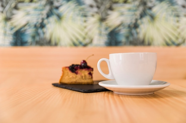 Cup of coffee with pastry on wooden surface Free Photo