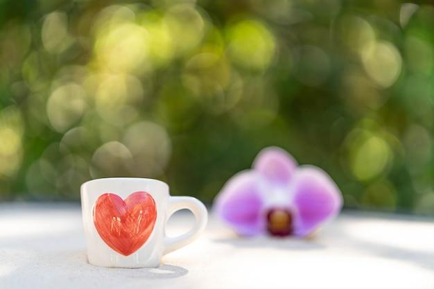 소프트 포커스 꽃 배경 모래에 인쇄 된 붉은 마음으로 컵 커피. 프리미엄 사진