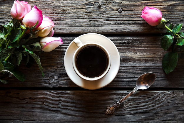 Cup of coffee with red rose and and copy space on wood background. breakfast on mothers day, women's day, valentine's day or birth day. hot drink, flowers Premium Photo