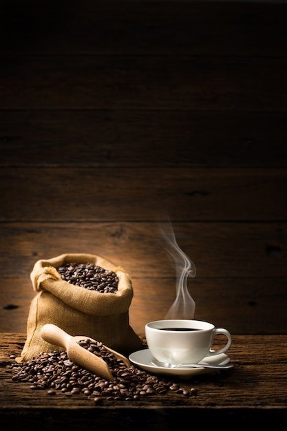Cup of coffee with smoke and coffee beans on old wooden background Premium Photo