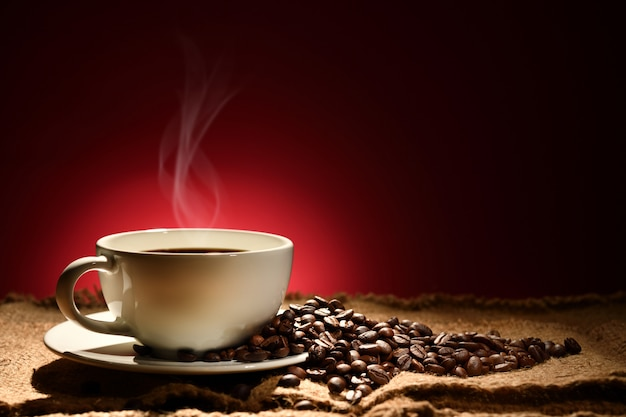 Cup of coffee with smoke and coffee beans on reddish brown background Premium Photo