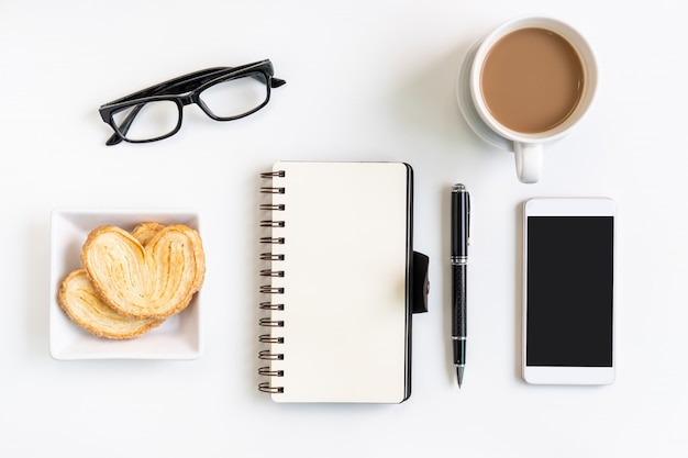 Cup of coffee with snacks, mobile phone and notebook on desk office with copy space, top view Premium Photo