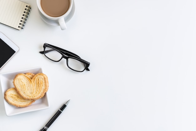 Cup of coffee with snacks and notebook on desk office with copy space, top view Premium Photo