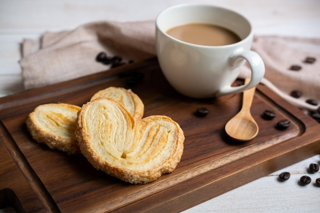 Cup of coffee with snacks on wooden cutting board on white wooden table Premium Photo