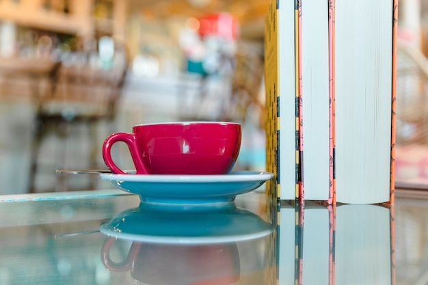 Cup of coffee with standing books on glass table Free Photo