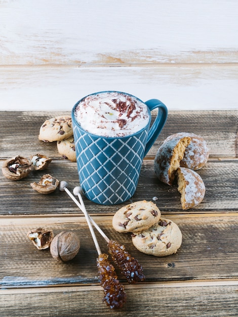 Cup of coffee with whipped cream and cookies on table Free Photo