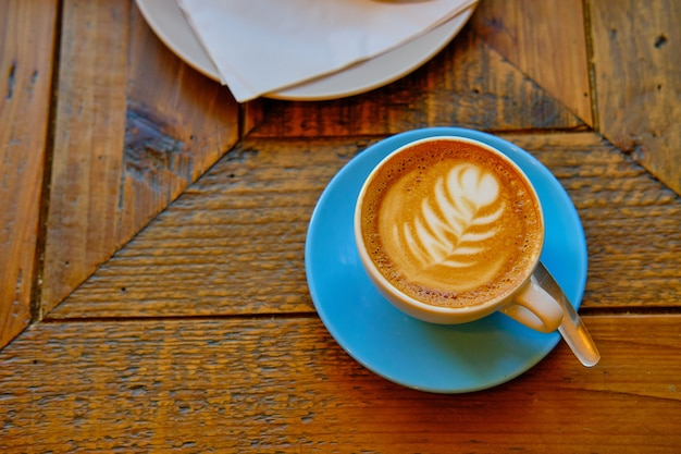Cup of coffee with a white flower decoration put on a wooden surface Free Photo