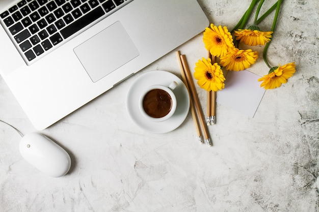 Cup of coffee with a yellow flowers and a laptop Premium Photo