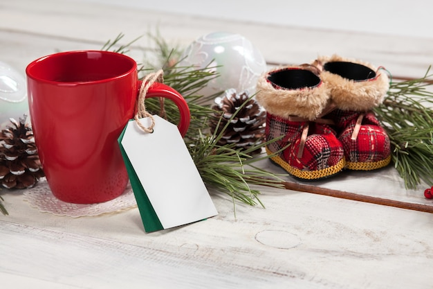 The a cup of coffee on the wooden table with a empty  blank price tag and christmas decorations. christmas mockup concept Free Photo