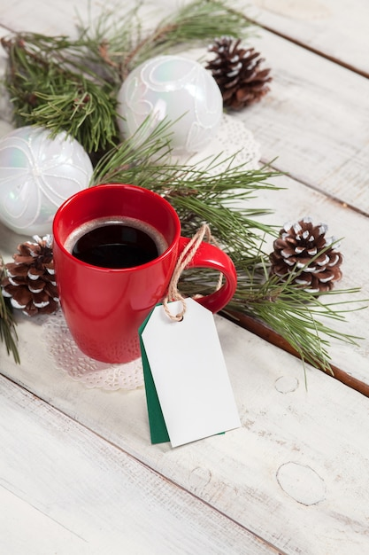 Cup of coffee on the wooden table with a empty  blank price tag and christmas decorations. Free Photo