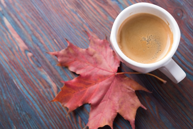 A cup of coffee on wooden table with fallen leaves. copyspace Premium Photo