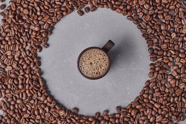 A cup of espresso in the middle of coffee beans. Free Photo