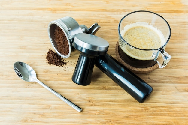 Cup of espresso on wooden board with ground coffee Premium Photo