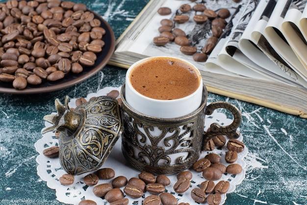 Tazza di caffè schiumoso, piatto di chicchi di caffè e libro sul tavolo di marmo. Foto Gratuite