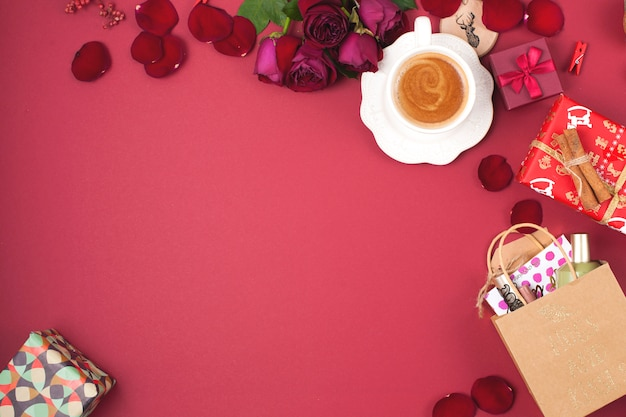 A cup of fragrant coffee and christmas decoration on a red background. roses, gifts and christmas surprises. top view. frame. copy spase Premium Photo