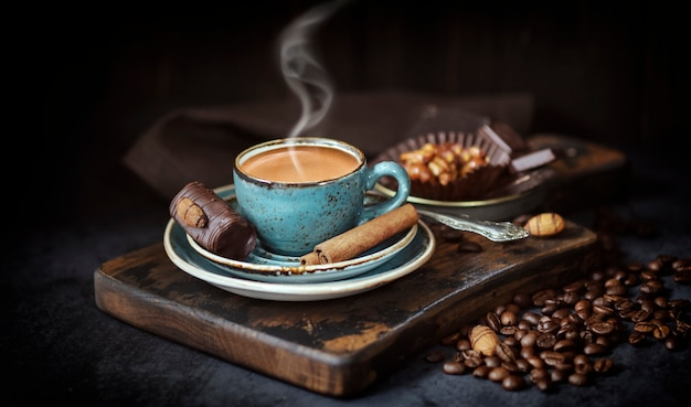 A cup of fragrant coffee on the of a rustic board with coffee beans and chocolate cake, a hot drink Premium Photo