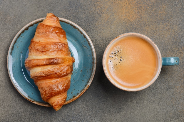 Cup of fresh coffee with croissant on concrete Premium Photo