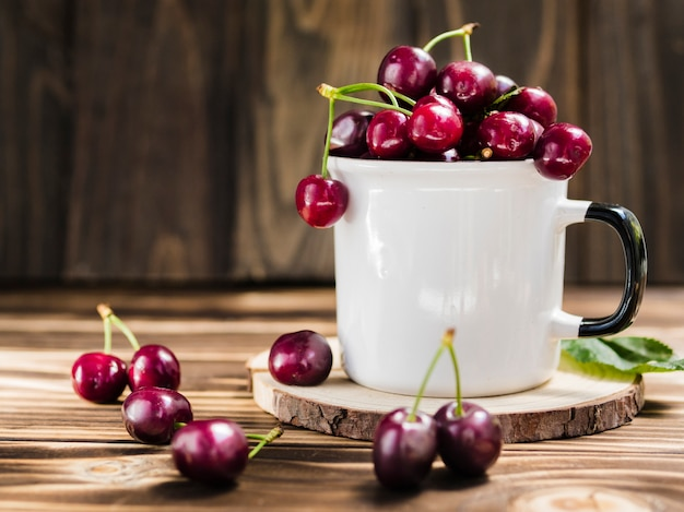 Cup of fresh sweet cherry on wooden background Free Photo