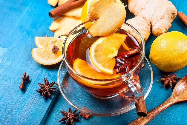 Cup of ginger tea with lemon and honey on dark blue, Premium Photo