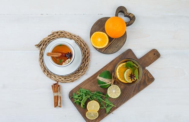 Tazza di tisana con agrumi, foglie di menta su taglieri e cannella su superficie bianca Foto Gratuite