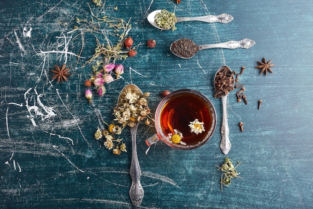 A cup of herbal tea with spices around. Free Photo