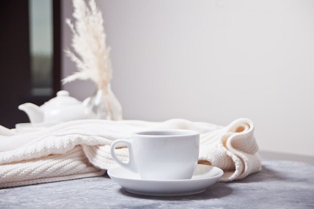Cup of hot aroma coffee and knittead white plaid and white teapot on the gray table Premium Photo