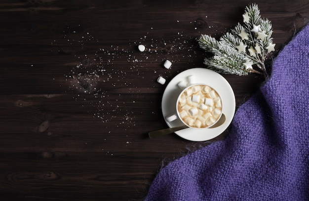 A cup of hot chocolate, a knitted blanket and spruce branches on a dark wooden background with snow. Premium Photo