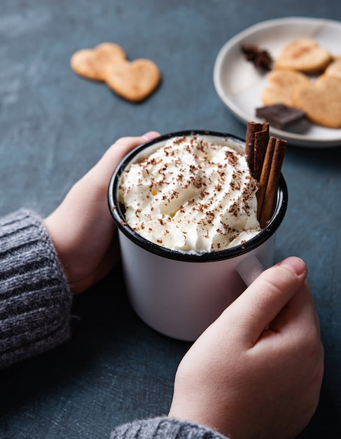 A cup of hot chocolate with cream and cinnamon  in  woman hand on a dark  table with homemade cookies. top view and close up Premium Photo