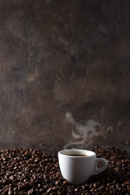 Cup of hot coffee on the background of coffee grains on a dark wooden background Premium Photo