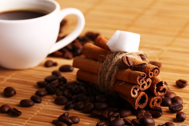 Cup of hot coffee and cinnamon sticks Free Photo