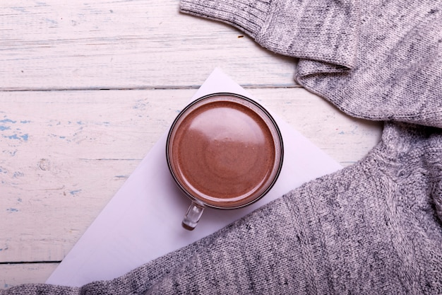 Cup of hot coffee or hot chocolate on rustic wooden table, closeup photo warm sweater with mug, winter morning concept, top view Premium Photo