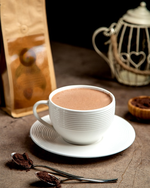 A cup of hot coffee served in white cup Free Photo