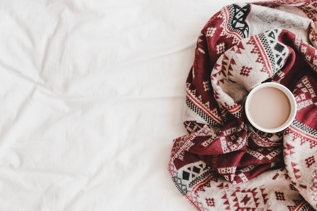 Cup of hot drink in patterned plaid on bedsheet Free Photo