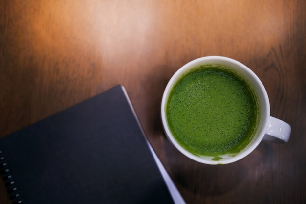 Cup of hot green tea latte and notebook on the table in house or cafe Premium Photo