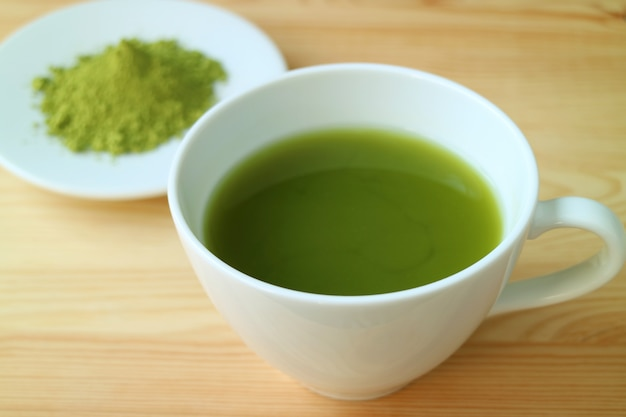 Cup of hot matcha green tea served on wooden table with blurry plate of matcha tea powder in background Premium Photo