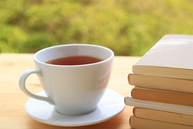 Cup of hot tea with pile of books on wooden table with blurred background of plants in garden Premium Photo