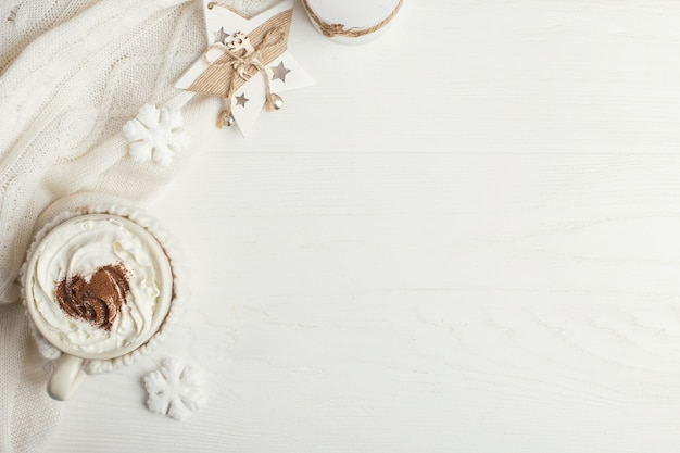 A cup of hot winter drink with whipped cream and scarf on a wooden table Premium Photo