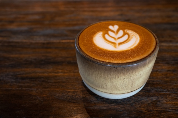 A cup of latte art coffee on wooden table Premium Photo