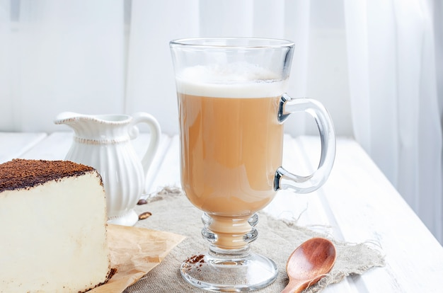 Cup of latte coffee with a piece of soft cheese in ground coffee Premium Photo