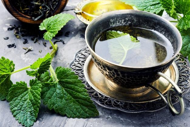 Chá de Melissa ao lado da planta. Ela faz parte dos chás que ajudam a dormir melhor.