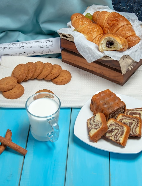 A cup of milk with cinnamon sticks and pastries on the table. Free Photo
