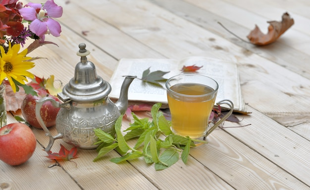 Cup of mint tea with flowers and mint leaf on a table Premium Photo